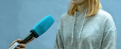Het meisje het blonde in een sporten lichte sweater geeft gesprekken Abstract beeld van een tiener De vrouwelijke overeenkomstige royalty-vrije stock fotografie