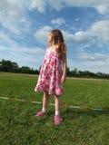 Het meisje, blonde kijkt op bewolkte blauwe hemel, rond haar gebiedsgreens Stock Afbeelding