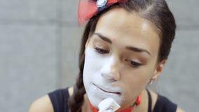 Het meisje bootst het toepassen van witte verf op haar gezicht vóór prestaties na stock video