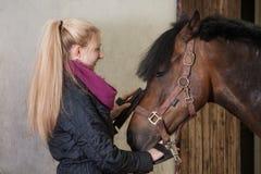 Het meisje borstelt haar poney Stock Foto
