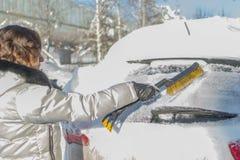 Het meisje borstelt het windscherm van de auto van de sneeuw Wi stock afbeeldingen
