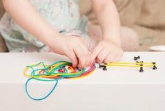 Het meisje bouwt vormen van gekleurde elastiekjes stock foto