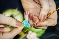 Het meisje breit een gehaakte bloem van blauwe draden tegen een backgr Royalty-vrije Stock Afbeelding