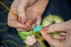 Het meisje breit een gehaakte bloem van blauwe draden tegen een backgr Royalty-vrije Stock Fotografie