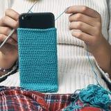 Het meisje breit een wollen smartphonegeval stock foto