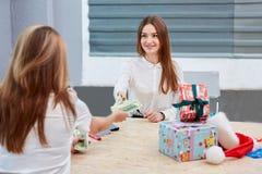 Het meisje brengt geld naar de beambte over royalty-vrije stock afbeeldingen