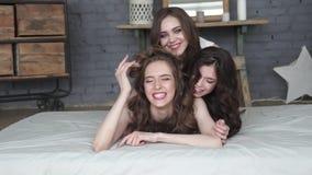 Het meisje brengt samen tijd door drie aantrekkelijke meisjes die bij bed en het glimlachen liggen Langzame Motie stock video