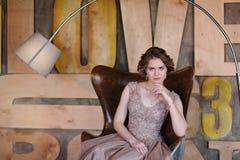 Het meisje het brunette in een mooie die kleding stelt zitting in een zetel tegen de achtergrond van de muur in de abstracte stij royalty-vrije stock afbeeldingen