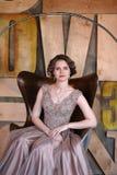 Het meisje het brunette in een mooie die kleding stelt zitting in een zetel tegen de achtergrond van de muur in de abstracte stij stock fotografie
