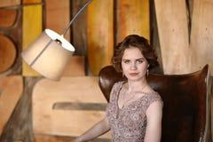 Het meisje het brunette in een mooie die kleding stelt zitting in een zetel tegen de achtergrond van de muur in de abstracte stij royalty-vrije stock afbeelding