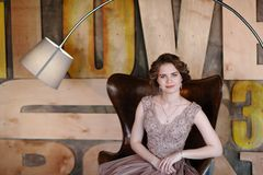 Het meisje het brunette in een mooie die kleding stelt zitting in een zetel tegen de achtergrond van de muur in de abstracte stij stock foto