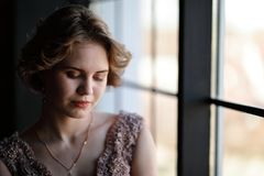 Het meisje het brunette in een mooie kleding stelt tegengesteld aan een venster royalty-vrije stock fotografie
