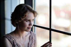 Het meisje het brunette in een mooie kleding stelt tegengesteld aan een venster stock fotografie