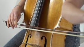 Het meisje buigt de cellokoorden om een lyrische samenstelling te spelen Sluit omhoog stock footage
