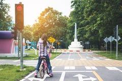 Het meisje cirkelt in het park, fietseinden bij verkeerslichten royalty-vrije stock foto