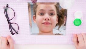 Het meisje, close-up, dacht in de spiegel na, door voorwerpen voor contactlenszorg wordt omringd, visie te verbeteren die royalty-vrije stock foto