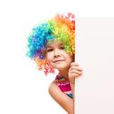 Het meisje in clown houdt lege banner Stock Afbeeldingen