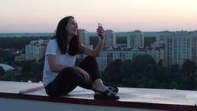 Het meisje communiceert door smartphone op het dak van een gebouw stock footage