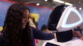 Het meisje communiceert met de robot en glimlacht Mens en robot Moderne robotachtige technologieën Kunstmatige intelligentie stock video