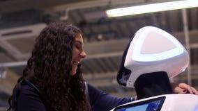 Het meisje communiceert met de robot en glimlacht Moderne robotachtige technologieën Kunstmatige intelligentie cybernetisch stock videobeelden