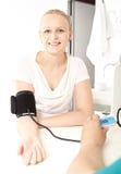 Het meisje controleert haar bloeddrukdruk. Stock Foto's