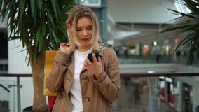 Het meisje controleert haar telefoon die zich met het winkelen zakken bevinden op haar schouder in de wandelgalerij stock videobeelden