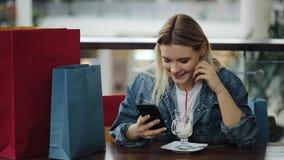 Het meisje controleert haar telefoonzitting met het winkelen zakken in de koffie stock videobeelden