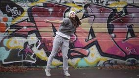 Het meisje danst in de straat tegen de achtergrond van graffiti stock videobeelden