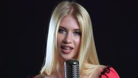 Het meisje danst en zingt in een retro microfoon Zwarte achtergrond Sluit omhoog stock video
