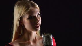 Het meisje danst en zingt in een retro microfoon Zwarte achtergrond Sluit omhoog Zachte nadruk stock video