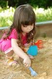 Het meisje dat aan een zandbak speelt Stock Foto's