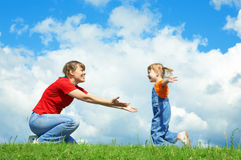 Het meisje dat aan moeder in werking wordt gesteld omhelst op groen gras royalty-vrije stock afbeelding