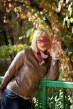 Het meisje dat een gezichts rode bladeren sluit royalty-vrije stock afbeelding