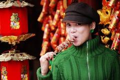 Het meisje dat van China gekonfijte vrucht eet Stock Afbeeldingen
