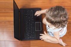 Het meisje dat van de baby een laptop computer met behulp van Royalty-vrije Stock Afbeeldingen