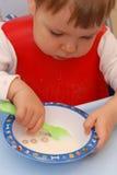 Het meisje dat van de baby graangewassen eet stock afbeelding