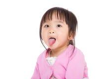 Het meisje dat van de baby grappig gezicht maakt stock afbeelding