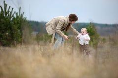Het meisje dat van de baby haar eerste stappen maakt Stock Foto's