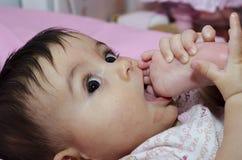 Het Meisje dat van de baby haar Teen zuigt Stock Foto