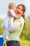 Het meisje dat van de baby houdend haar gelukkige moeder kust Stock Afbeeldingen