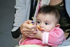 Het Meisje dat van de baby met haar Moeder eet Stock Foto