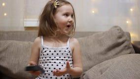 Het meisje dat van de baby op TV let Het kind zet de televisie aan gebruikend ver stock footage