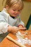 Het meisje dat van de baby pret met het koekje heeft royalty-vrije stock fotografie