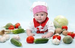 Het meisje dat van de babykok chef-kokhoed met verse groenten draagt. Stock Afbeeldingen