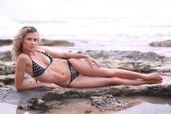 Het meisje dat van de bikini op een kustrots ligt Royalty-vrije Stock Afbeeldingen
