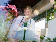 Het meisje dat van de blonde in bloemenwinkel werkt stock afbeeldingen