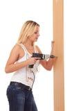 Het meisje dat van de blonde de muur boort Stock Fotografie