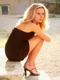 Het meisje dat van de blonde zwarte miniskirt draagt royalty-vrije stock afbeelding