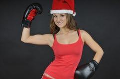 Het meisje dat van de kerstman bokshandschoenen draagt Stock Foto's