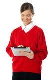 Het meisje dat van de school het nieuwe apparaat van het aanrakingsstootkussen met behulp van Royalty-vrije Stock Afbeeldingen